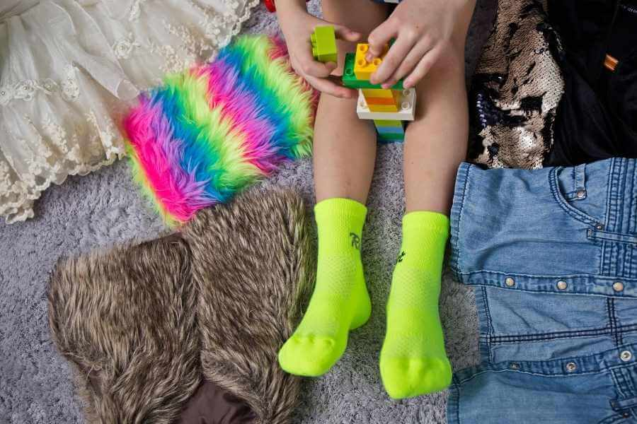 Kid's feet on the bed, neon socks, blanket