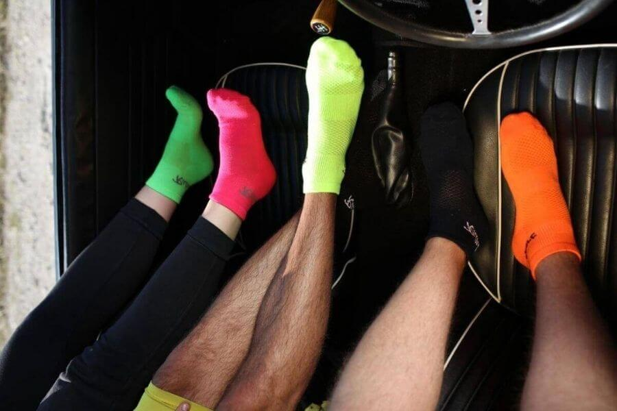 Legs of three people wearing colourful socks, in a car.