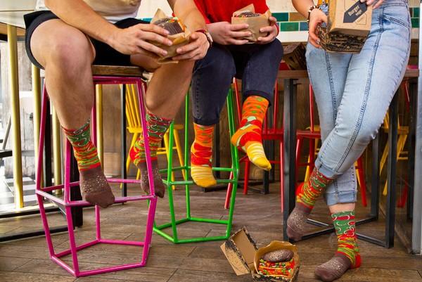 A group of men eating vegan food, wearing Rainbow Socks products