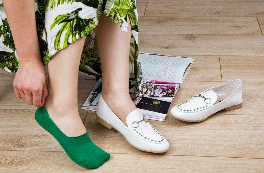 A woman in green invisible socks taking off white shoes