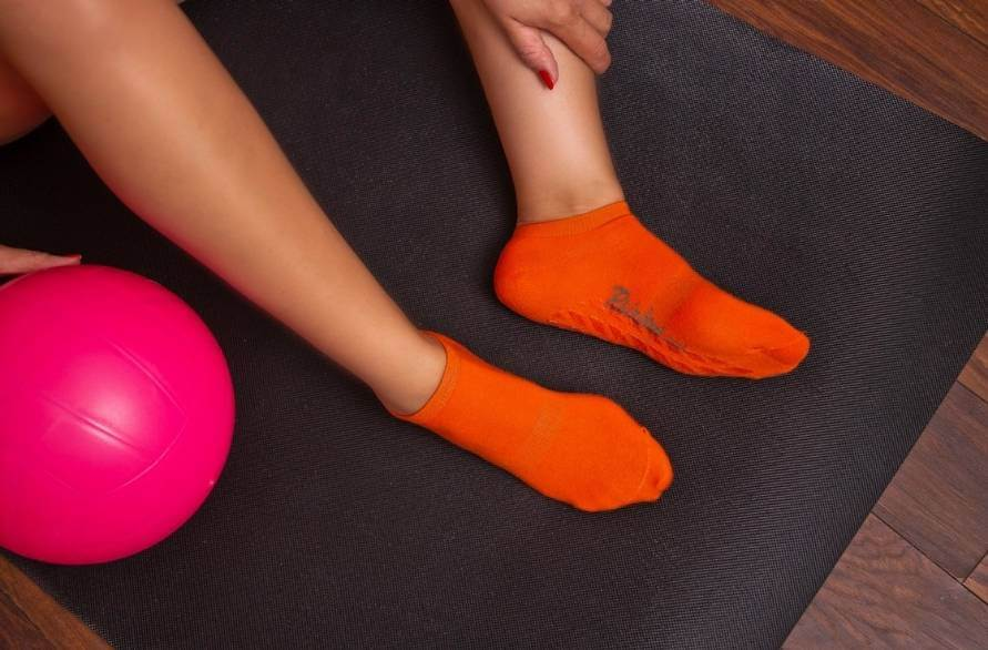 A person's legs and feet in indoor Rainbow Socks during exercise on a mat.