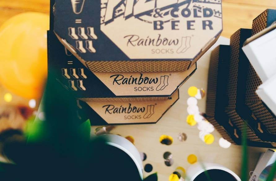 Boxes of pizza and beer Rainbow Socks sets arranged on top of each other like real pizza boxes.